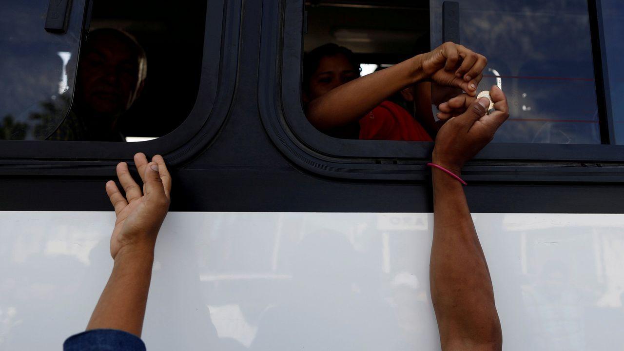 Un grupo de migrantes centroamericanos piden dinero a los viajeros de un microbús para desplazarse a la oficina del Instituto Nacional de Migración de México