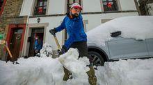 Vecinos de la localidad asturiana de Pajares, que está en nivel rojo con lo que se prohíbe la circulación de vehículos articulados, camiones y autobuses, retiran la nieve de los caminos.
