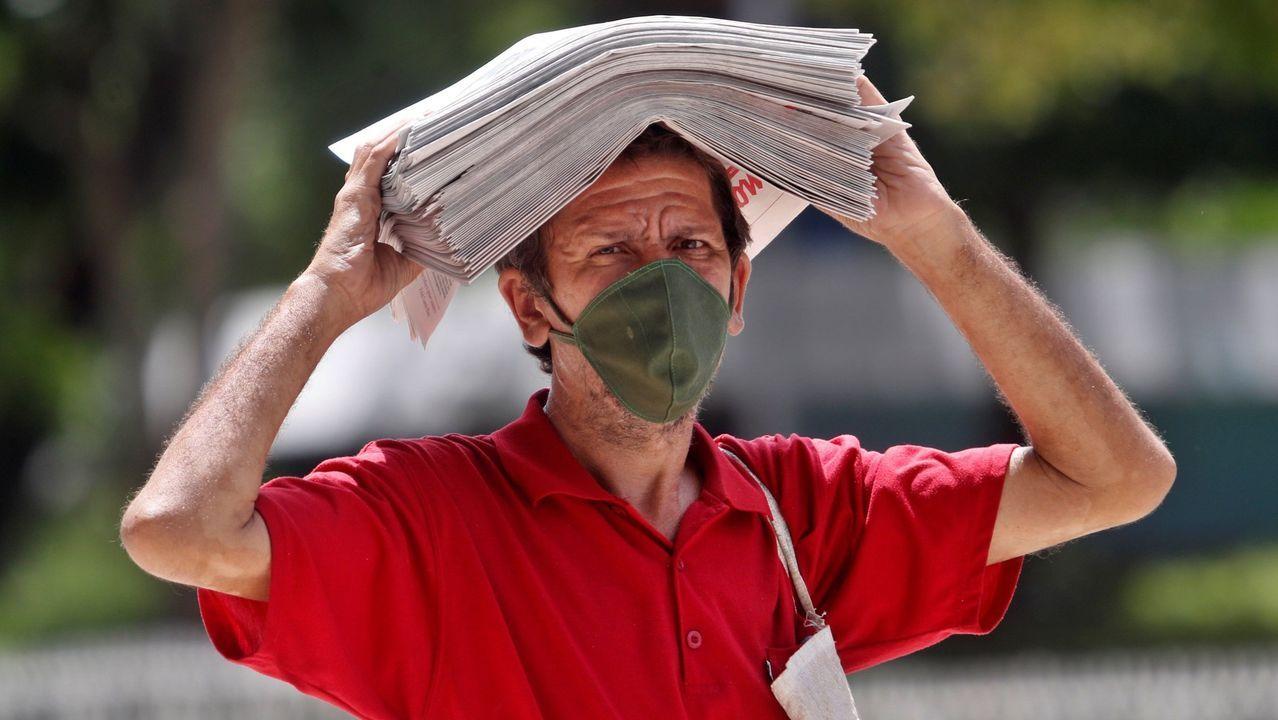 Un vendedor callejero se protege del sol con varios periódicos Granma.