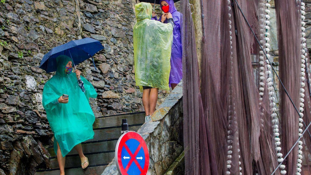 Un grupo de turistas visita Cudillero, bajo una intensa lluvia