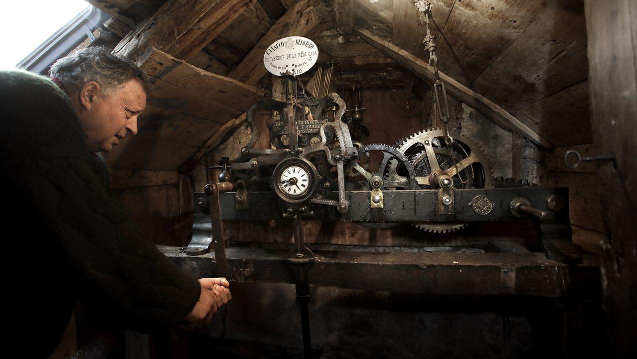 Los vecinos de un pueblo de Os Ancares dan cuerda a un reloj de casi 120 años