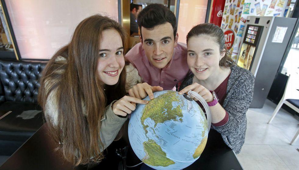 Gabriela González, Juanjo Roca y Lara Pazos, ayer en Pontevedra, señalan en la bola del mundo sus destinos para el próximo curso.