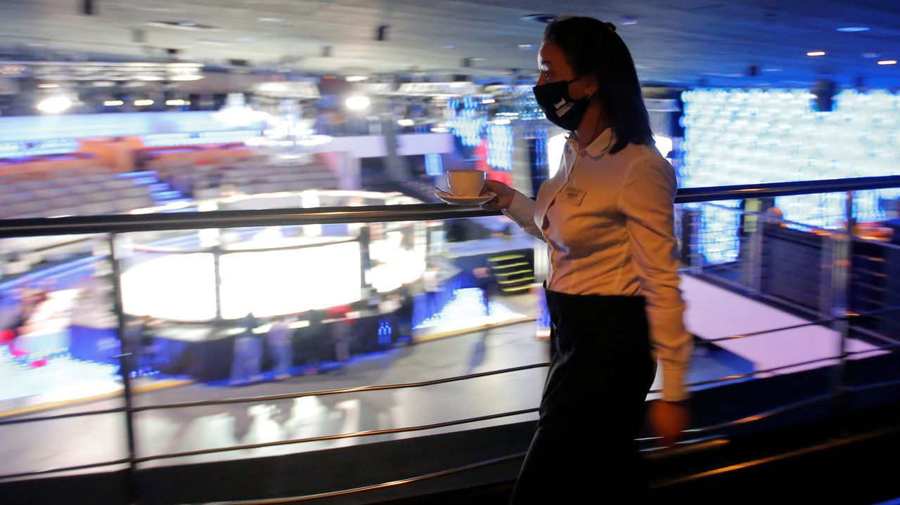 Una camarera bielorrusa lleva un café a una de las escasas mesas de espectadores del campeonato nacional de lucha, sin público en las gradas