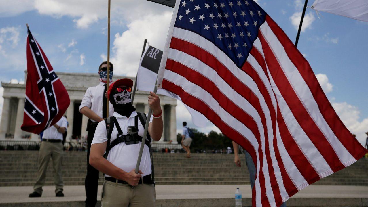 Un manifestante sostiene una bandera de EE.UU. delante de otros que agitan una bandera confederada y otras banderas vinculadas a la supremacía blanca