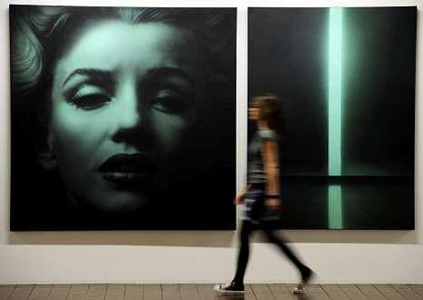 Angelina Jolie - Sexy.Una mujer pasa ante un retrato de Marilyn en una obra del artista ruso Timofeev.