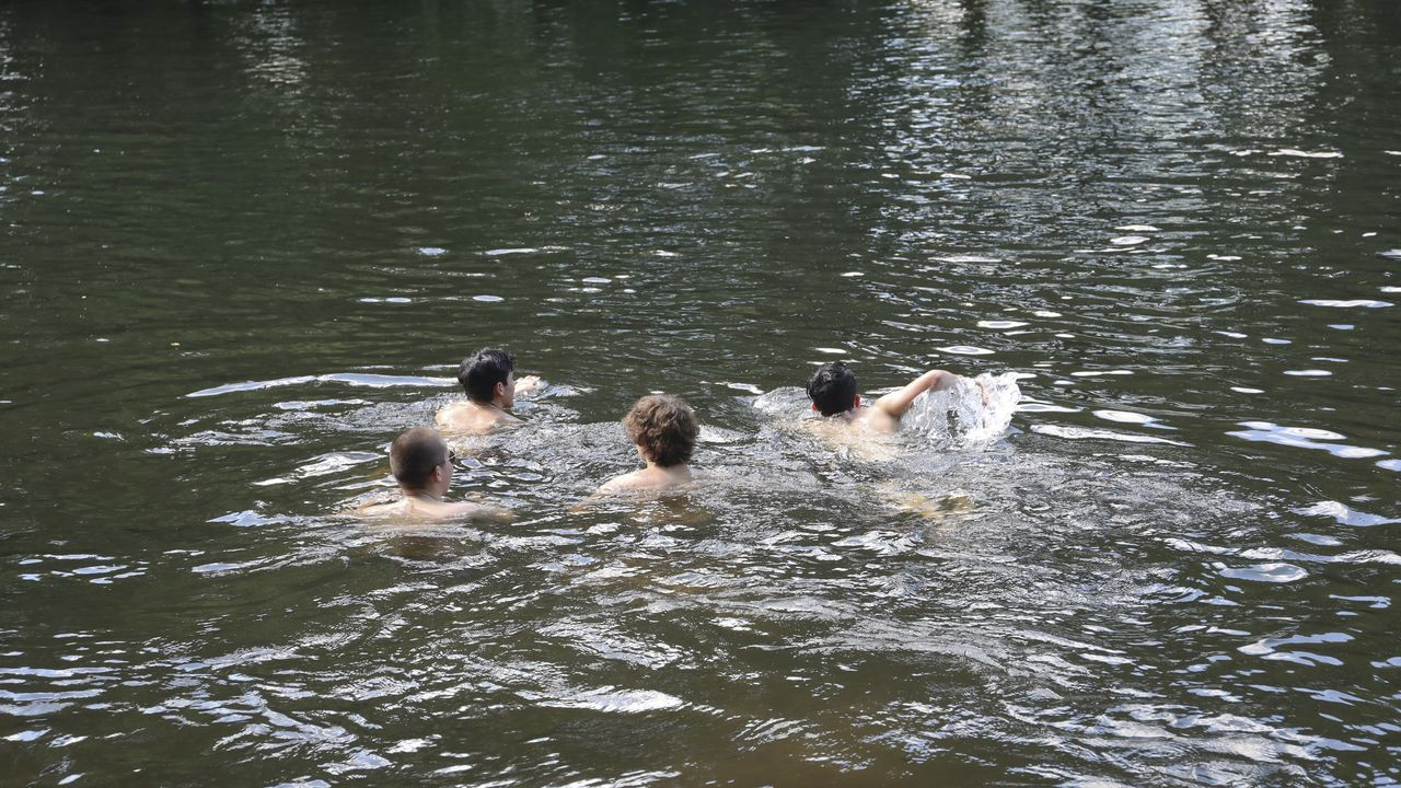 Calor y bañistas en la playa fluvial de Chaián, en el Tambre