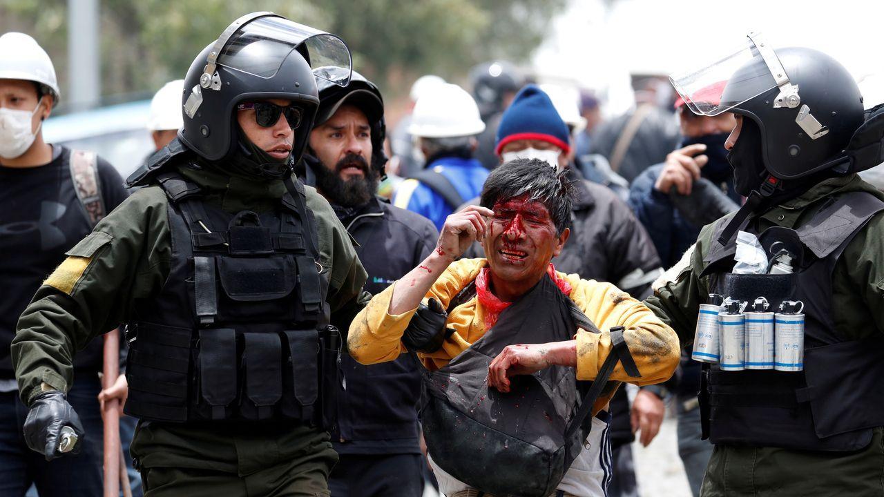 Las fuerzas de seguridad detienen a un hombre herido tras los enfrentamientos este lunes entre seguidores de Evo Morales y opositores en La Paz