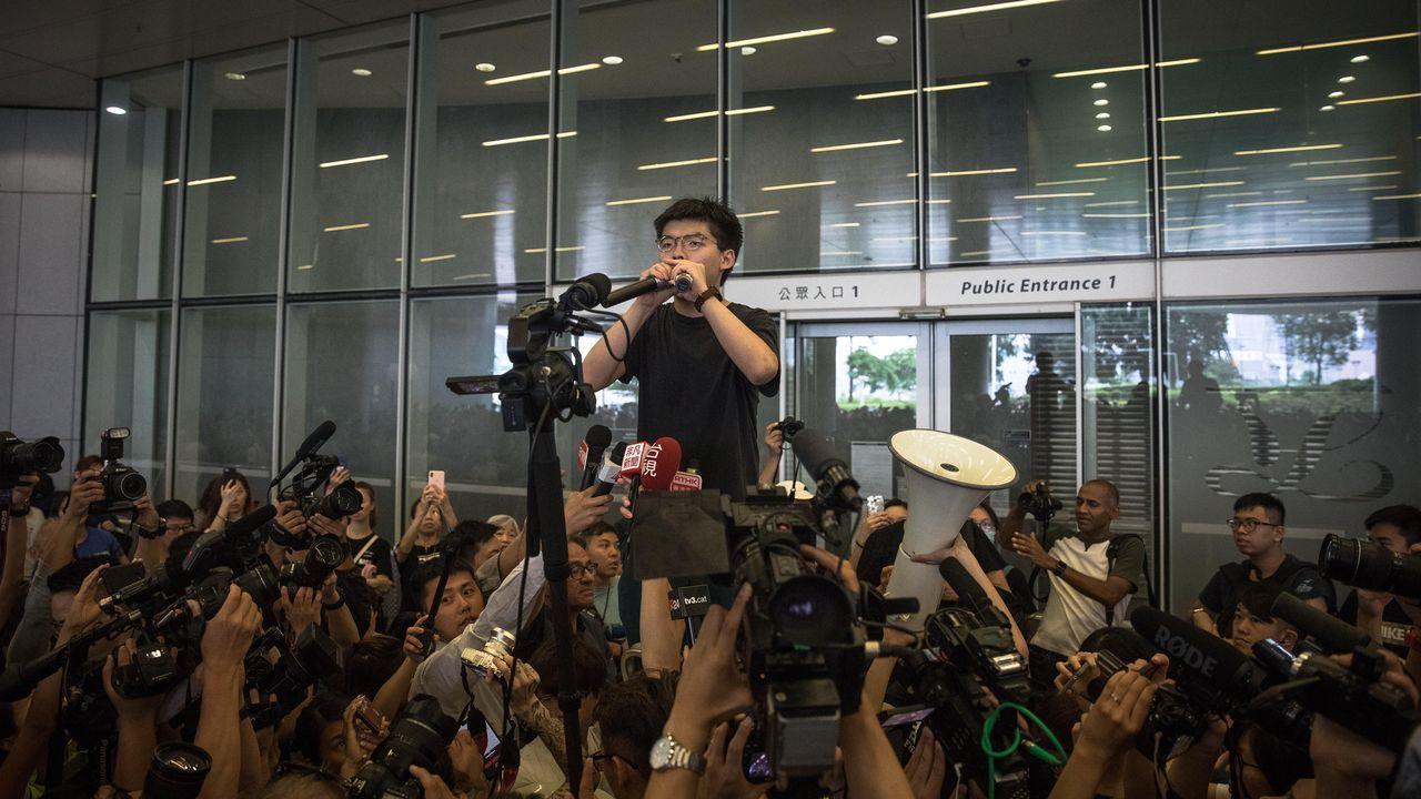 Joshua Wong, uno de los líderes de la Revolución de los Paraguas, fue recibido entre grandes aplausos y aclamaciones por la multitud congregada ante el Parlamento