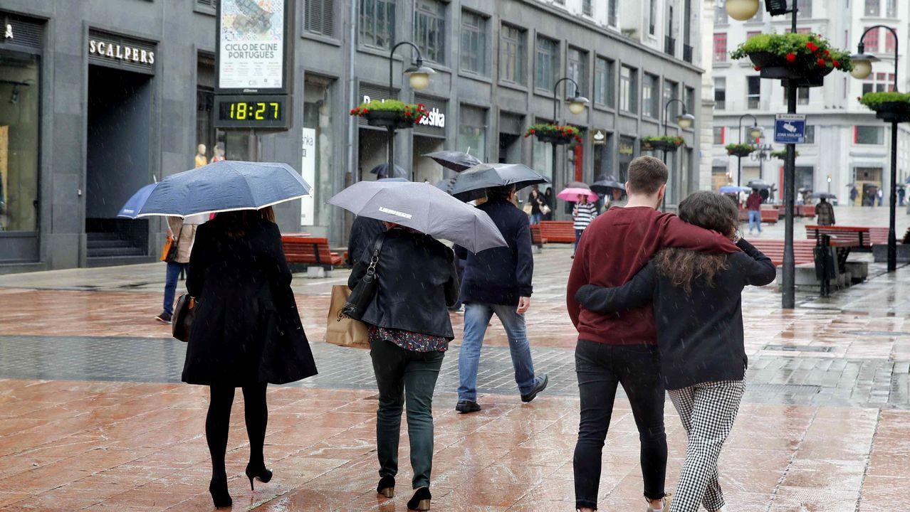 Un grupo de pescadores recoge el «campanu» del Sella, el segundo del día, capturado por Juan Antonio González, el «sastrín», en el Barcu de Arriondas..Una calle de Oviedo bajo la lluvia