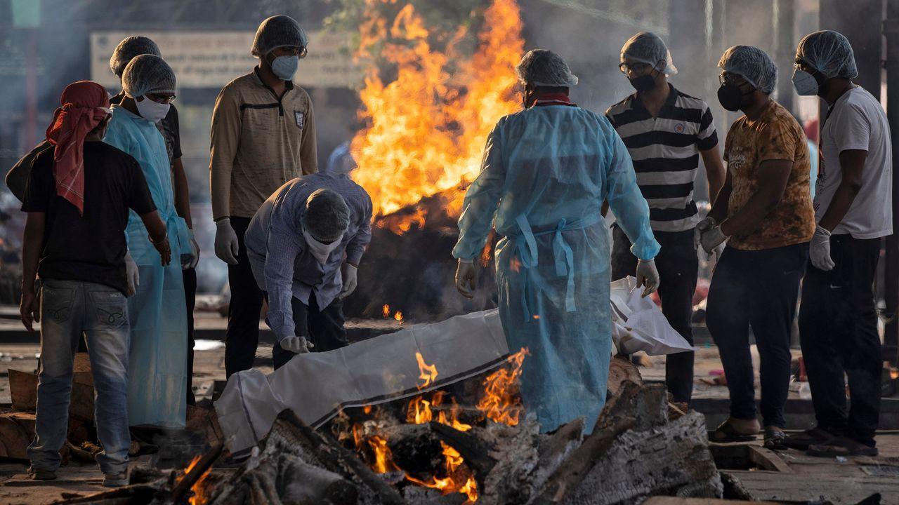 En lndia un grupo de personas asiste a la cremación de un fallecido por coronavirus