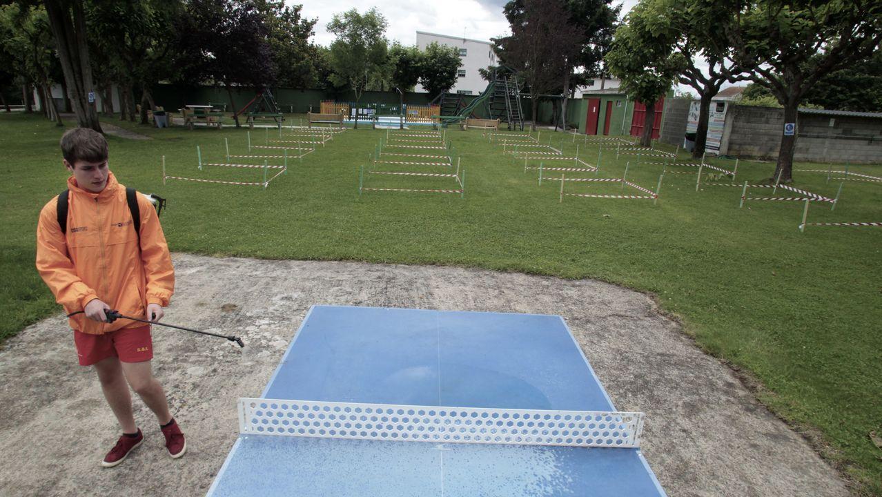 Un socorrista desinfecta una mesa de ping-pong junto a la zona de césped de las piscinas con las parcelas acotadas