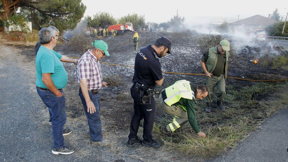 Un integrante de la brigada de investigación forestal de la Xunta, agachado en el lugar en el que según los vecinos empezó uno de los incendios de Moreda