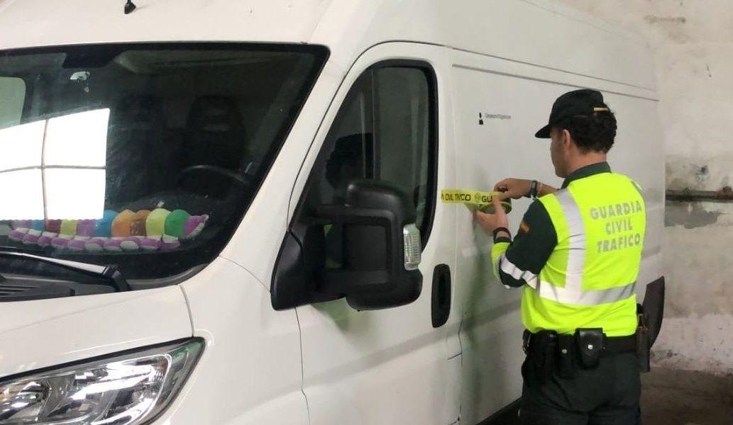 Un guardia civil coloca un precinto en la furgoneta incautada a un conductor de Ferrol que fue denunciado hasta cinco veces por saltarse el confinamiento