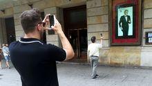 Dos hombres fotografían la efigie de Arturo Fernández en la fachada del Teatro Jovellanos de Gijón