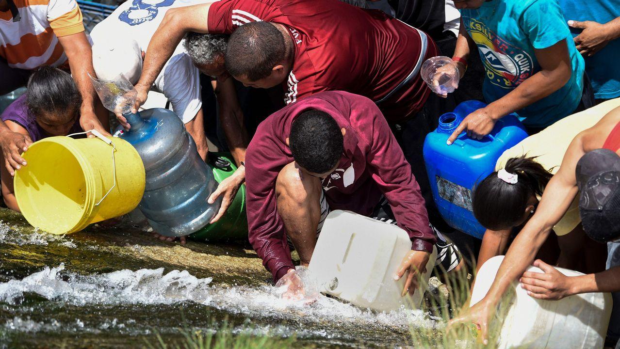 Vecinos de Caracas recogen agua del río Guaire ante los problemas de desabastecimiento