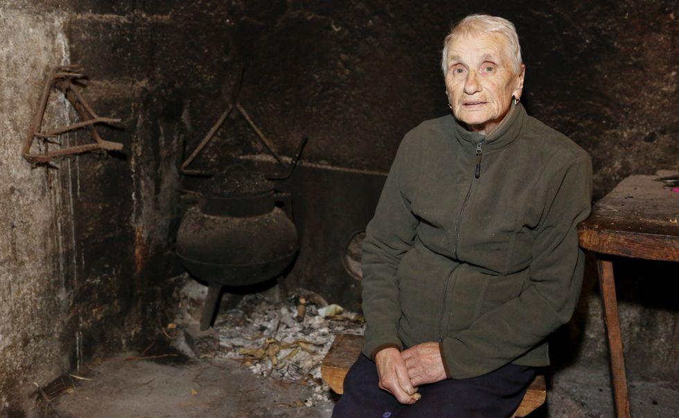Aos seus 85 anos, Dolores Macías -na lareira da súa casa-, sempre ten unha copla nos beizos.