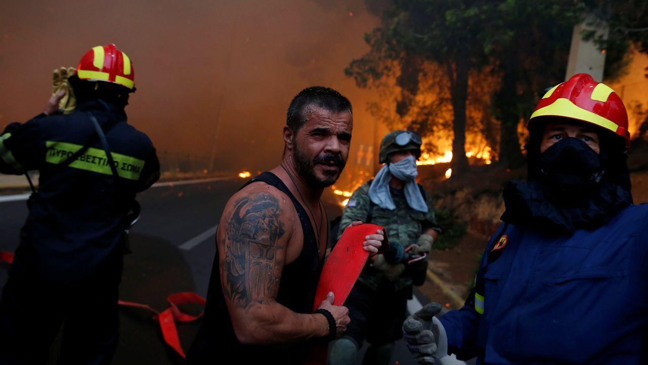 Bomberos, soldados y residentes locales llevan una manguera durante un incendio forestal arde en la ciudad de Rafina, cerca de Atenas