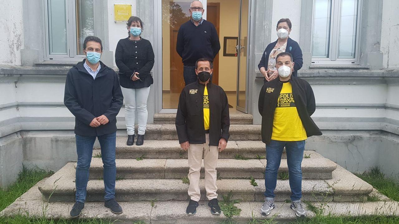 Viveiro vuelve al nivel alto de restricciones por coronavirus.El alcalde (izquierda) y son dos concejalas de Cervo, con miembros de Fol do Raxal, ante las antiguas escuelas