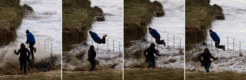 Una pareja sorprendida por un golpe de mar en la playa de Esteiro, Xove