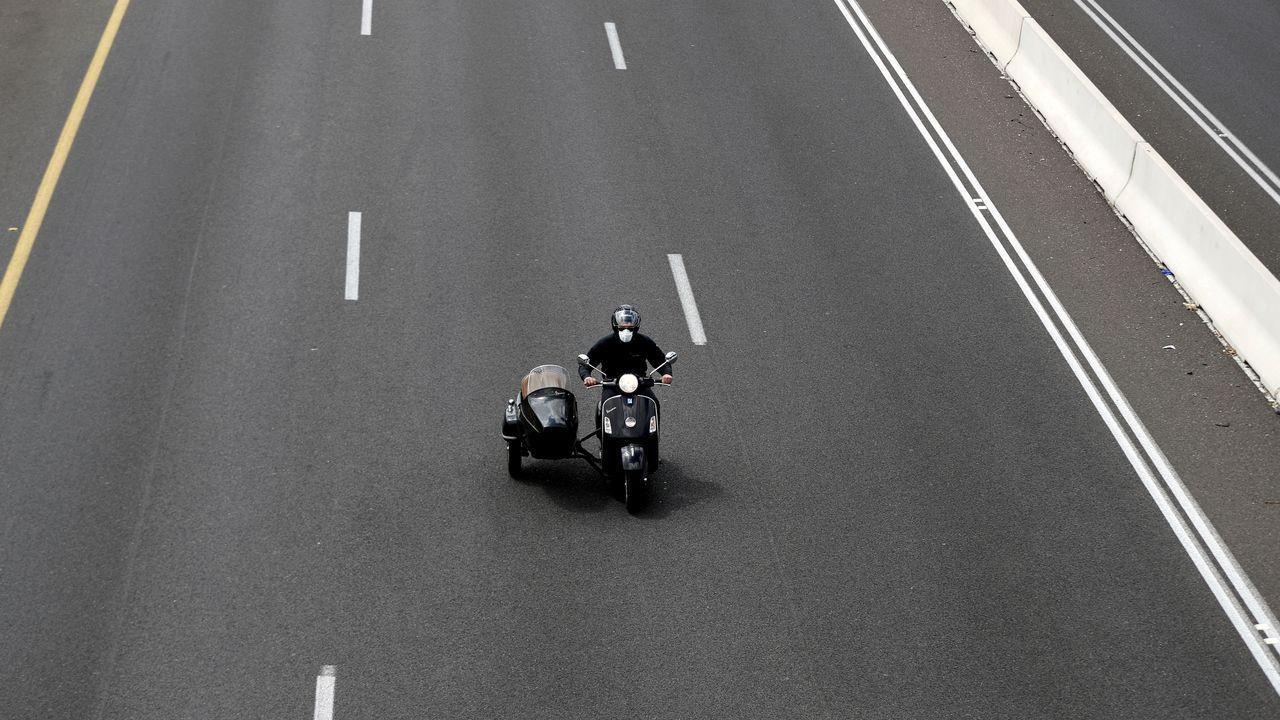 Un hombre con mascarilla conduce una moto en Israel