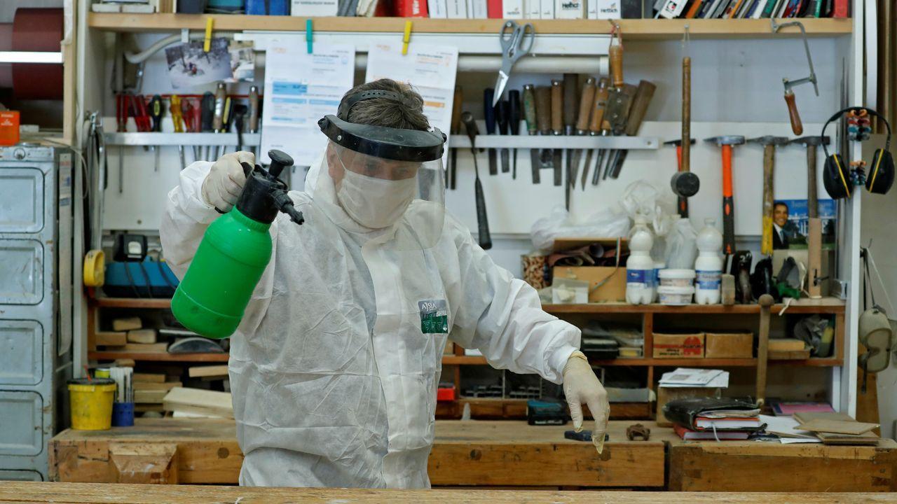 Un carpintero italiano desinfecta su carpintería para prepararla para la vuelta al trabajo
