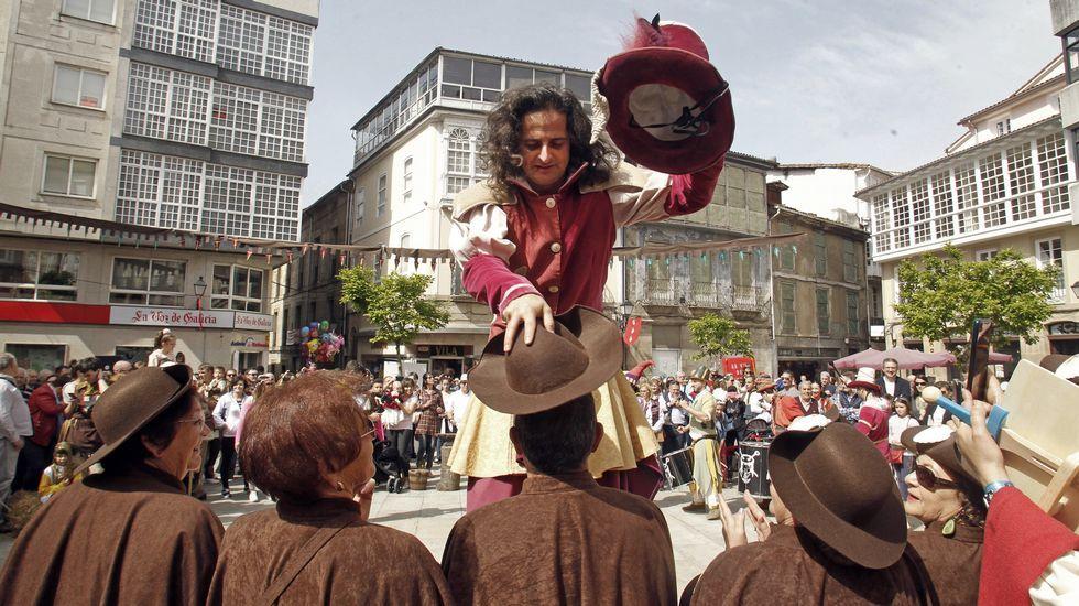 Un equilibrista sobre zancos bromea con los integrantes de la asociación Camiños a Santiago pola Ribeira Sacra en la Feira Medieval de Monforte