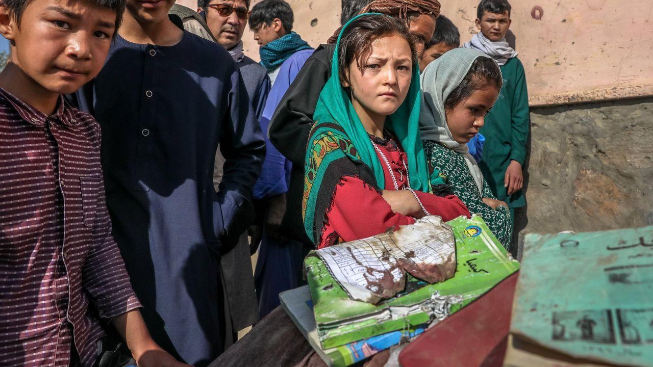 Un grupo de escolares vigilan los libros y cuadernos  manchados de sangre de sus compañeros muertos en el atentado en la escuela de Kabul