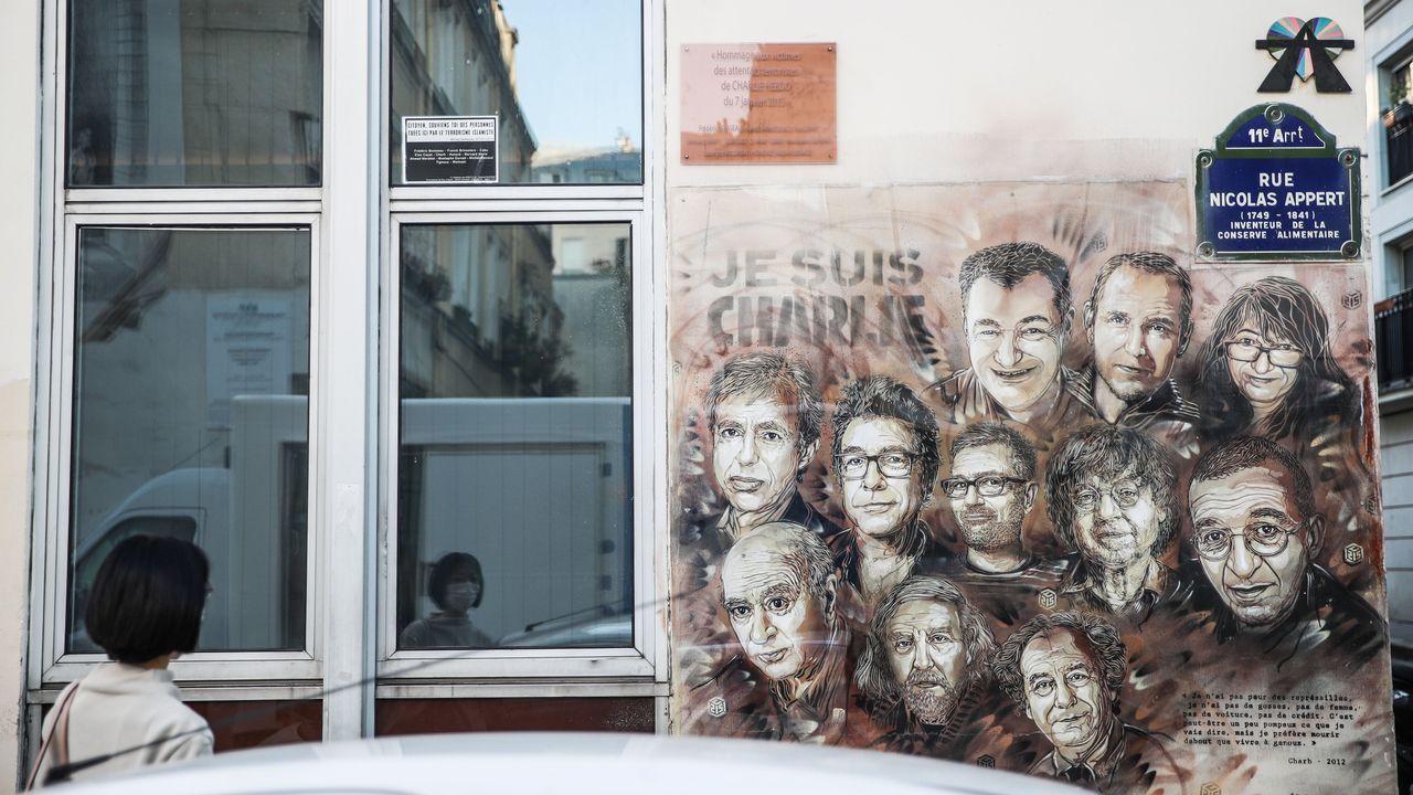 Una mujer observa una ilustración en la pared de los miembros del equipo de «Charlie Hebdo» asesinados en el 2015