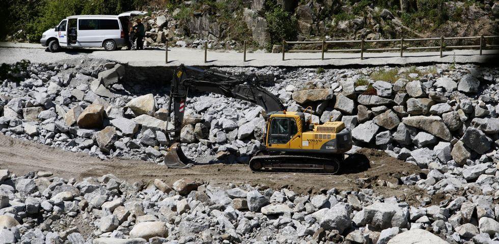 Una excavadora trabaja sobre el terreno para recolocar las grandes rocas desplazadas por el agua hace tres meses.