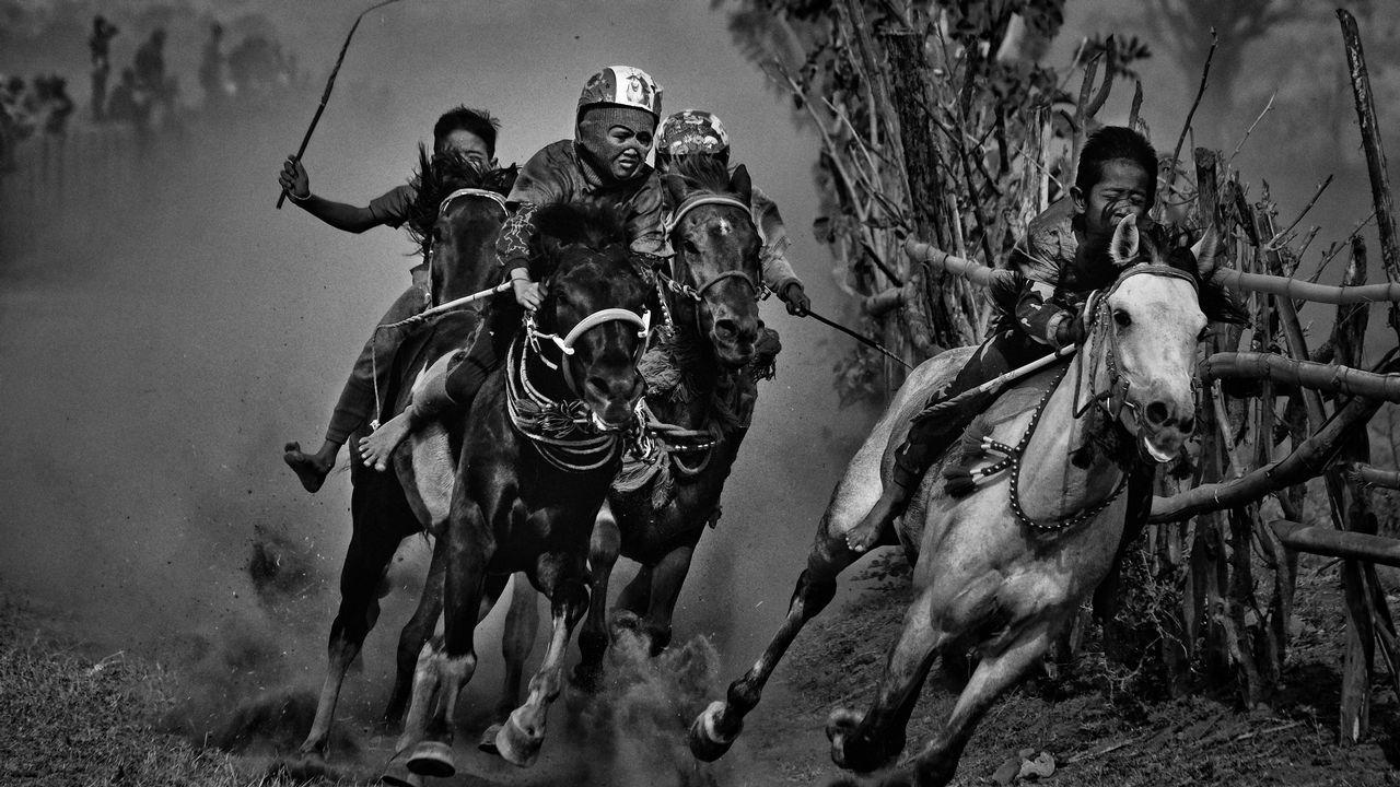 Fotografía cedida por la organización World Press Photo, que muestra la imagen captada por el fotógrafo Alain Schroeder, ganador del 1er premio de la categoría «Sports - Stories». La foto muestra a jóvenes jinetes que compiten en una carrera de caballos de Maen Jaran, en la isla de Sumbawa, Indonesia, el 17 de septiembre del 2017.