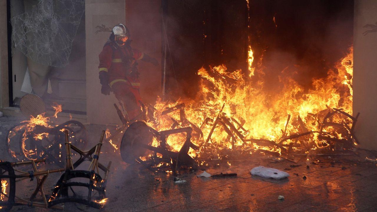 El desastre, la extinción del fuego y el recorrido por las cenizas, en fotos.Incendio ante un comercio de los Campos Elíseos durante la manifestación del pasado sábado