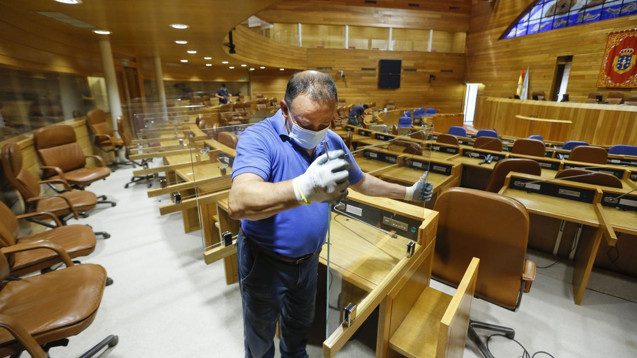 Un operario poniendo mamparas de separación en el Parlamento, esta semana