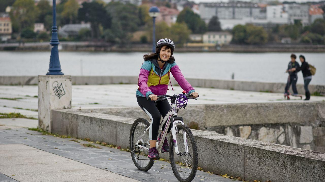 Raquel con su bici por el paseo marítimo de O Burgo