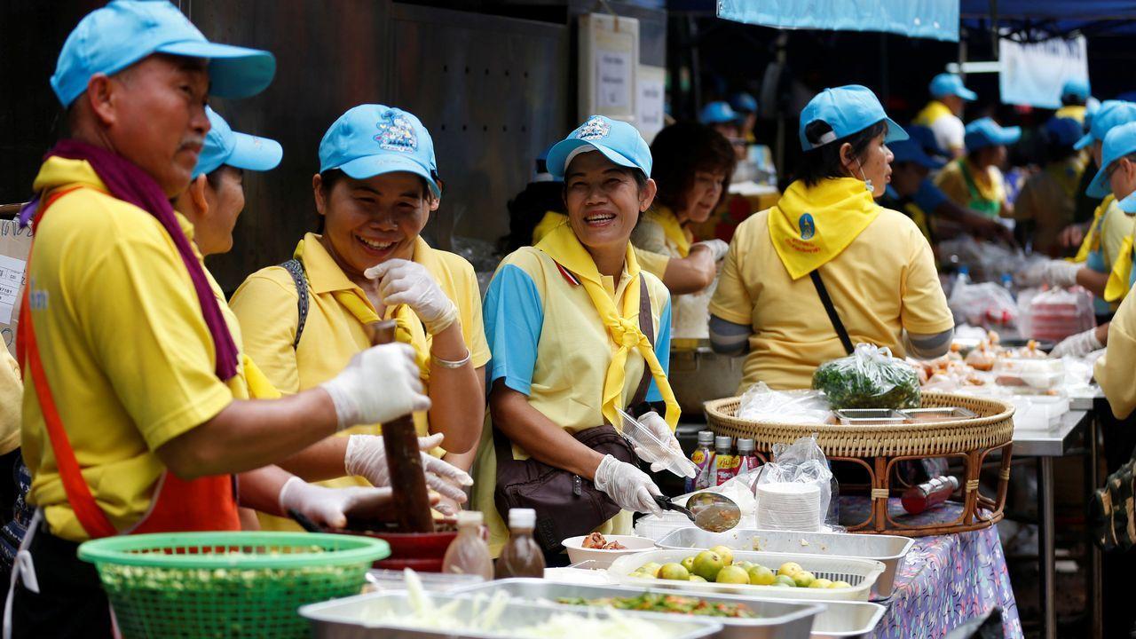 Voluntarios entregan comida gratis cerca de la cueva Tham Luang.