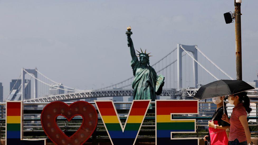 Mujeres llevando mascarilla pasean por delante de la replica de la estatua de la libertad de Tokio