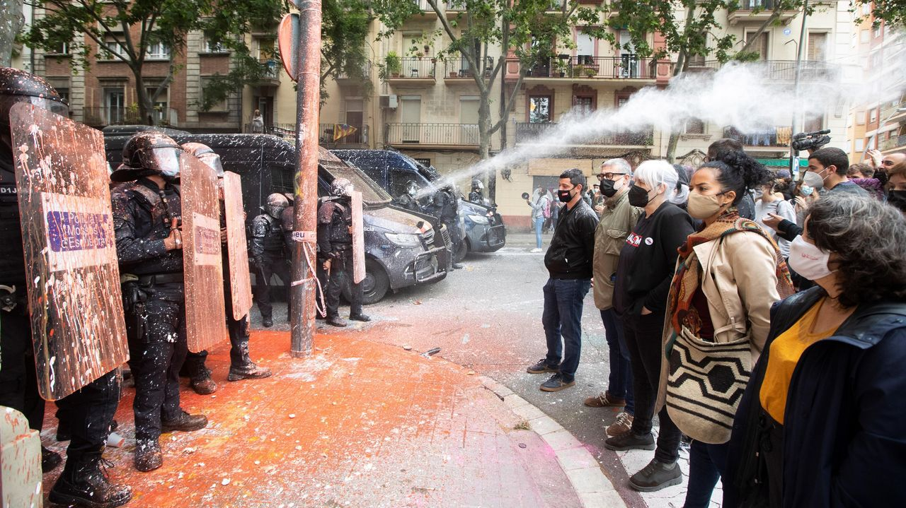 Los diputados de la CUP Carles Riera y Dolors Sabater, segunda y tercero a la derecha en la imagen, frente a unos agentes de los Mossos durante un deshaucio en Barcelona