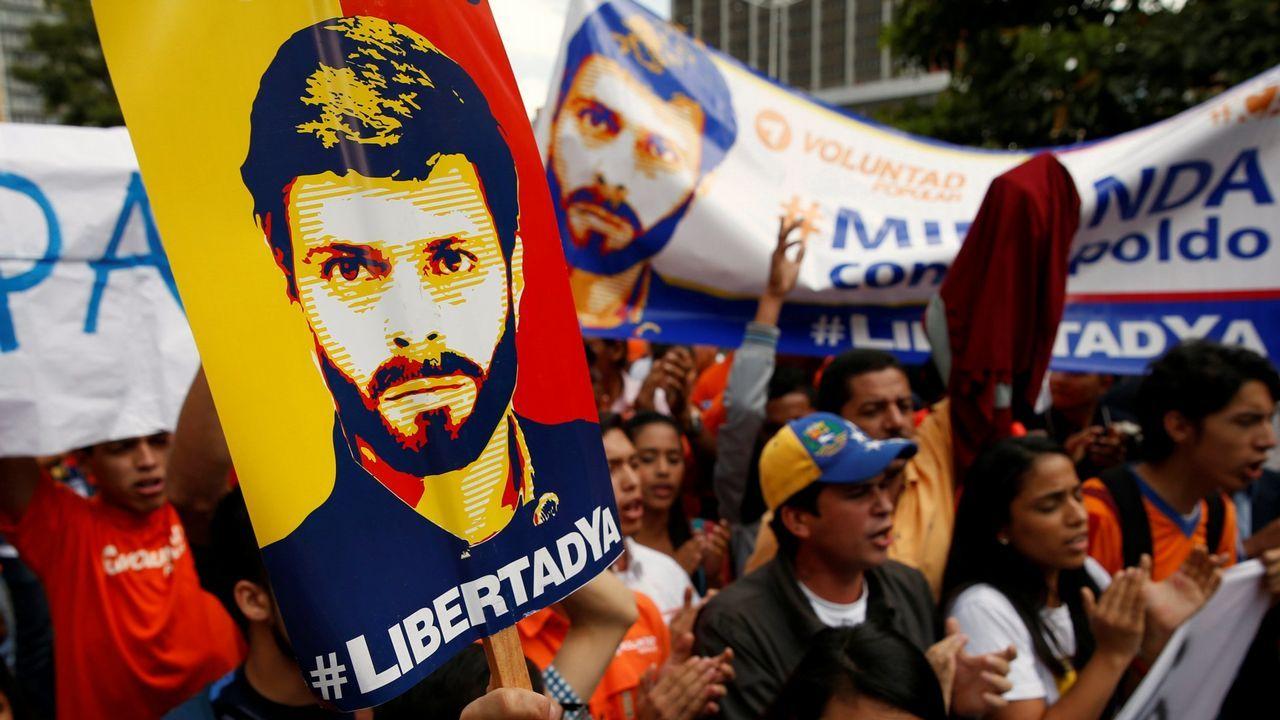 Leopoldo López saluda a sus simpatizantes desde la valla de su casa.Dos mujeres yacen en el suelo tras un enfrentamiento entre chavistas y opositores