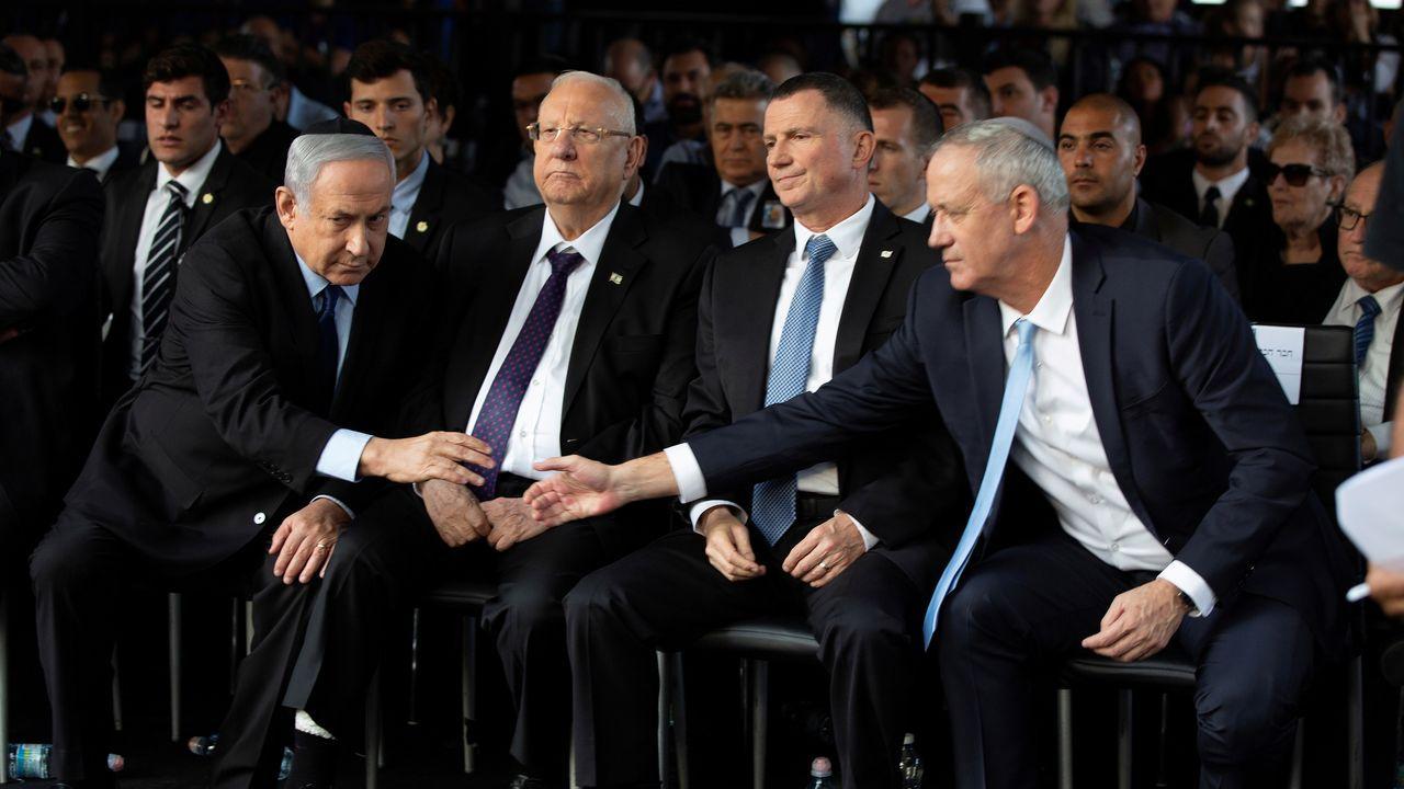 Netanyahu y Gantz se estrechan la mano, durante un acto el pasado noviembre
