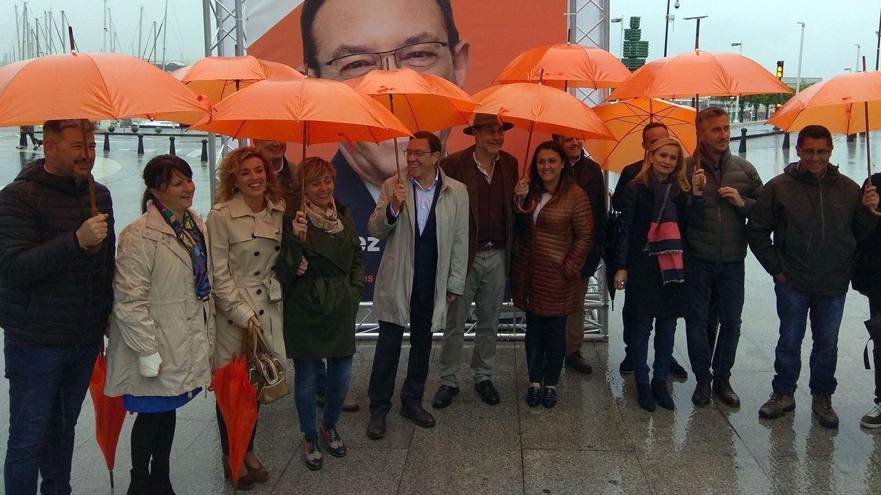 Juan Vázquez inicia la campaña en Gijón, acompañado por los miembros de su lista y protegido de la lluvia con unos llamativos paraguas naranja