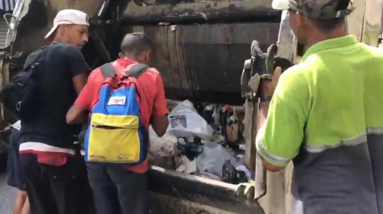 Gente buscando comida en la basura