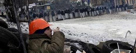 La tensión sigue en aumento en Ucrania.Un manifestante come en una barricada mientras los antidisturbios montan guardia en las calles de Kiev, cuya ocupación transcurrió ayer sin incidentes.