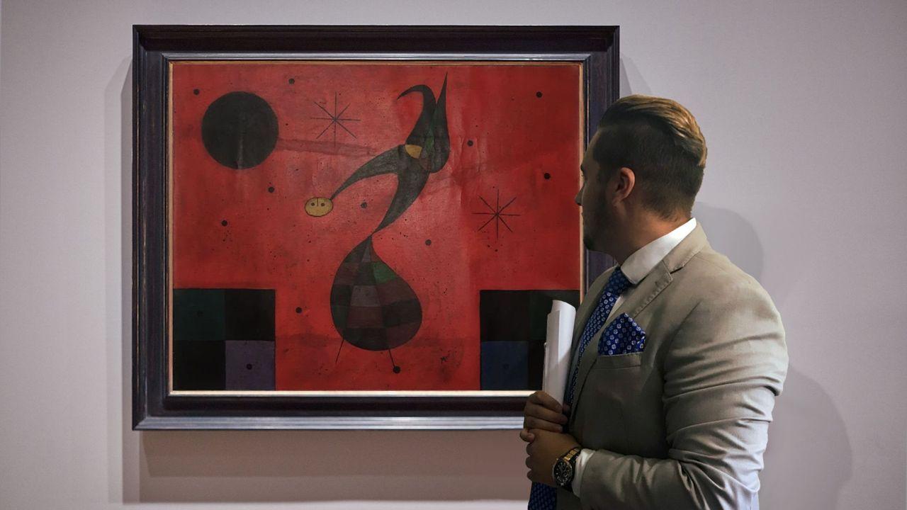 El marchante Cristian López, ante el cuadro «Oiseau en le nuit» , de Joan Miró.