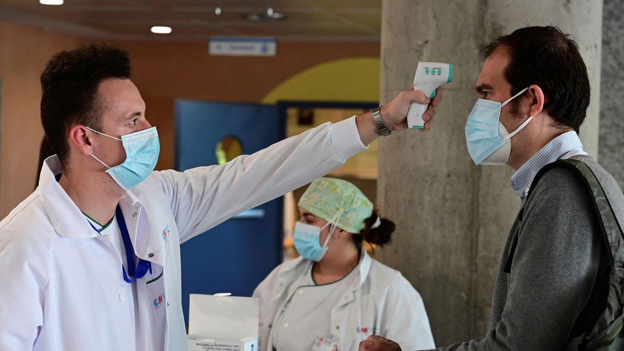 Un sanitario mide la temperatura a un hombre que accede al hospital de Alcorcón, en Madrid