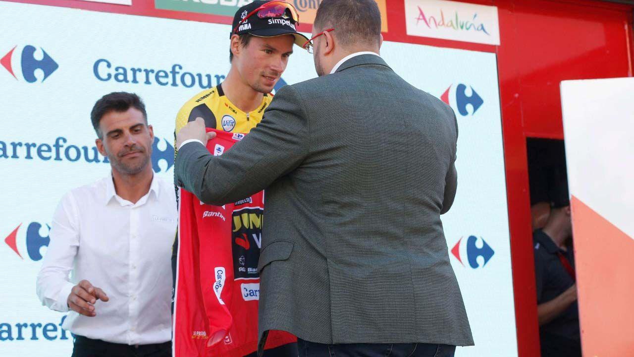 El presidente del Principado de Asturias, Adrián Barbón, entregando al esloveno Primoz Roglic el jersey rojo que le acredita como líder de la Vuelta.