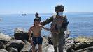 Un militar español ayuda a un menor migrante a salir del agua en la playa del Tarajal