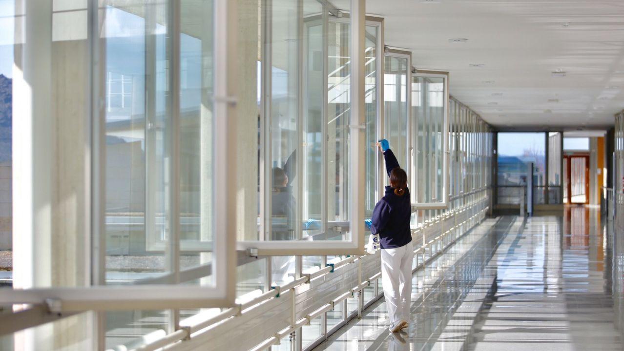Una mujer protegida con paraguas y mascarilla camina por una calle del centro de Oviedo