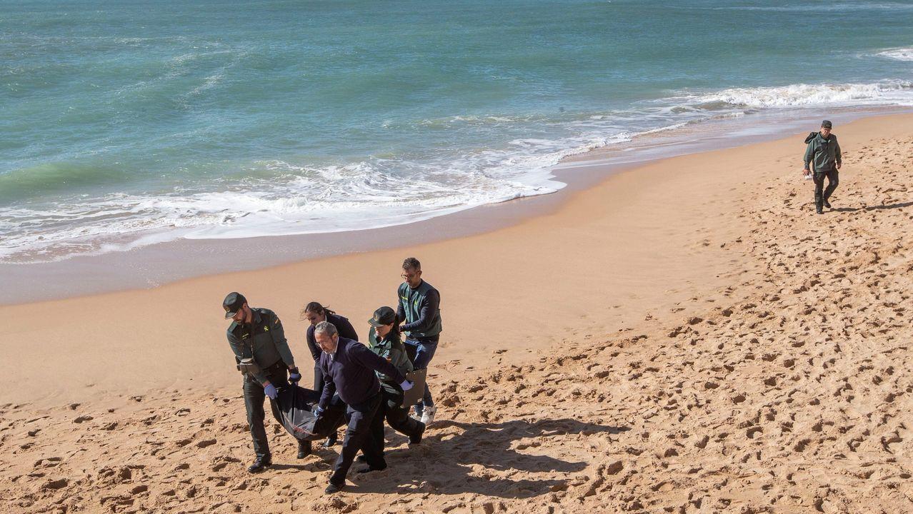 Agentes de la Guardia Civil y operarios, trasladan un cadáver de los ocupantes de la patera que naufragó en el 2018 en la playa de Caños de Meca (Cádiz)