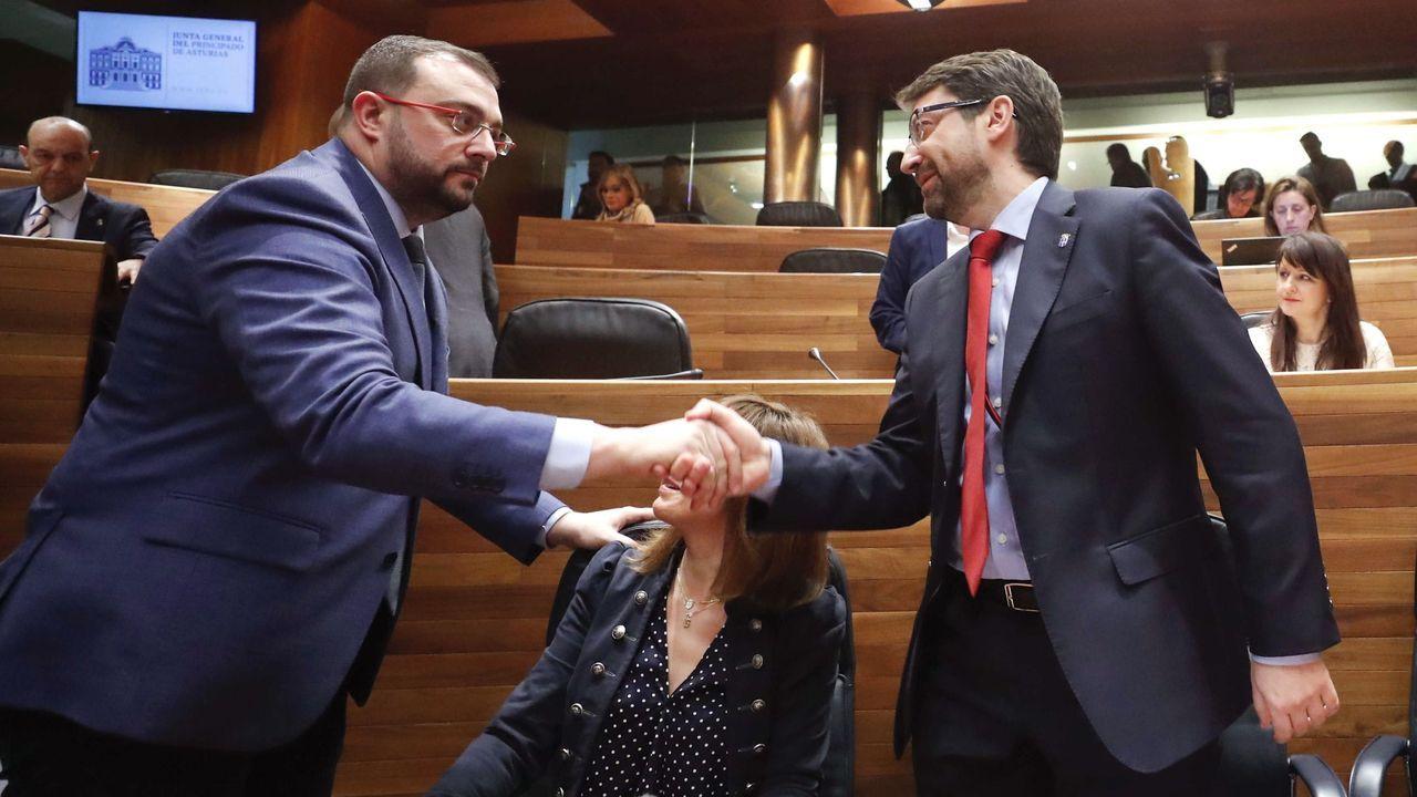 El presidente. del Principado, Adrián Barbón, saluda al consejero de Industria, Empleo, y Promoción Económica, Enrique Fernández (d), en la JUnta General del Principado