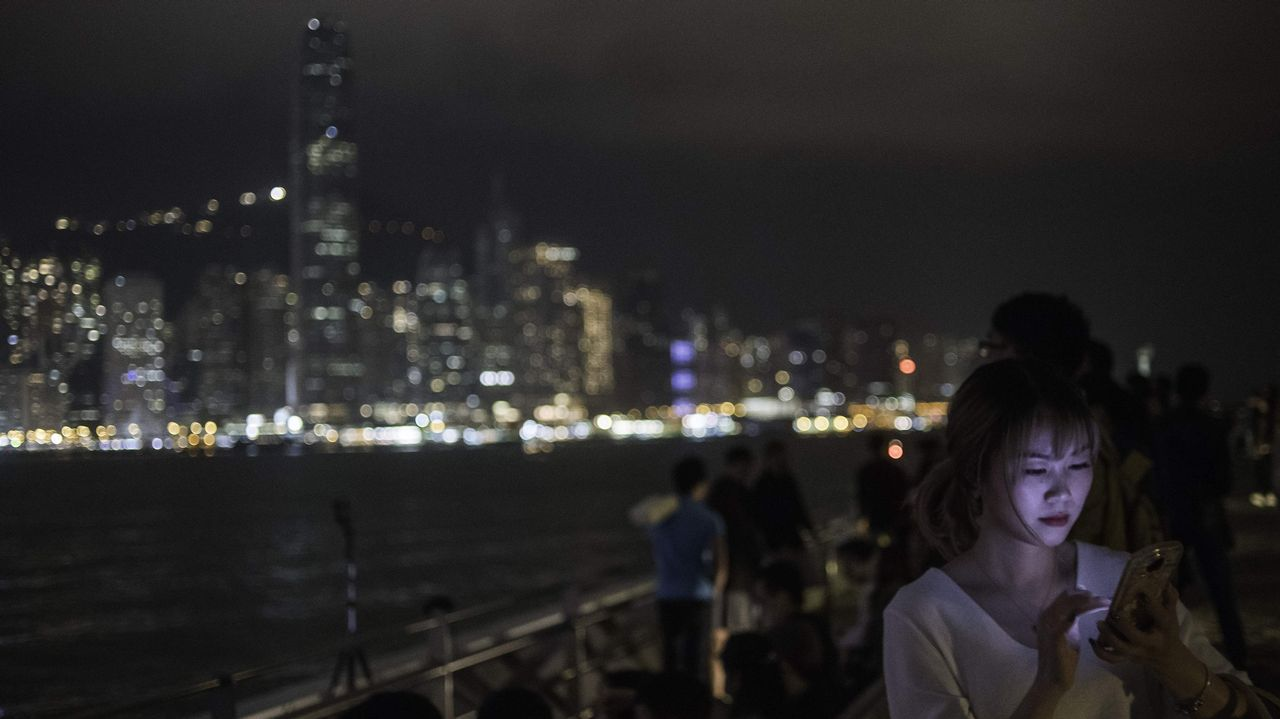 Una mujer observa su móvil de espaldas al skyline de Hong Kong, durante el apagado de luces