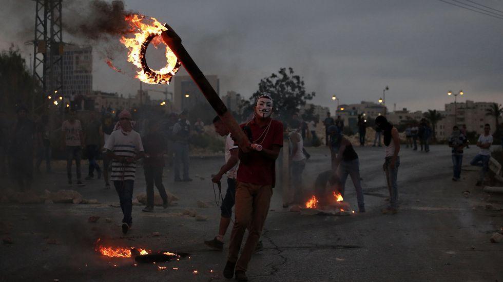 Un joven palestino quema neumáticos durante los choques con el ejército israelí.